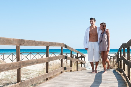 Happy beautiful young couple walking together at summer tropical beach photo