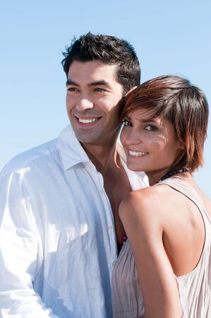latin look: Beautiful young couple smiling together in a sunny summer day