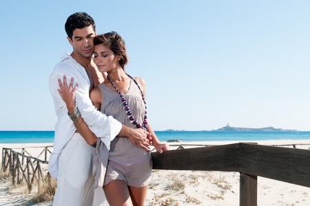 Sweet young couple flirting together at summer beach photo