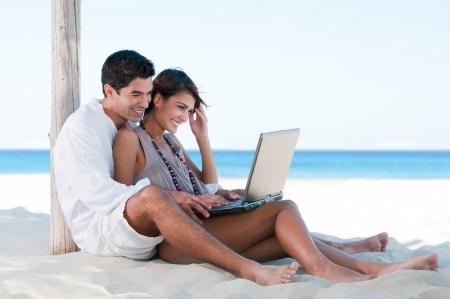 chica surf: Sonriendo feliz pareja navegan por la red y disfrutar el verano en playa tropical