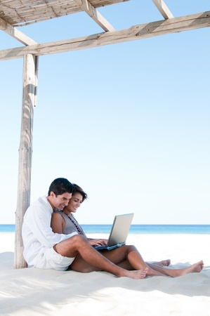 woman laptop happy: Beautiful young couple surfing the net together during summer vacation at tropical beach Stock Photo