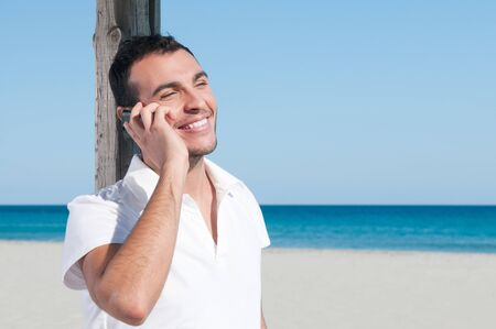 Happy smiling young man talking on mobile at summer beach photo