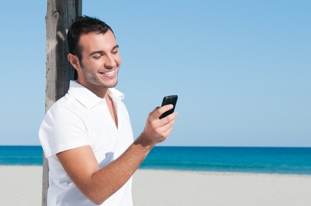 sms: Happy young man looking at news and messaging on his smart phone at beach Stock Photo