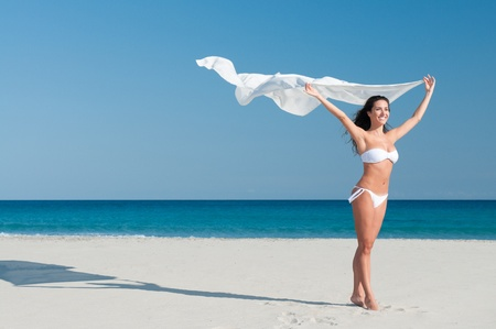 Beautiful smiling young woman blowing white cloth in the breeze of a summer day photo