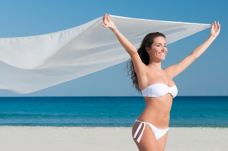 Beautiful smiling young woman blowing white cloth in the breeze of a summer day Stock Photo - 8857176