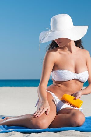 Beautiful young woman applying protective lotion before sunbathing at beach Stock Photo - 8857184