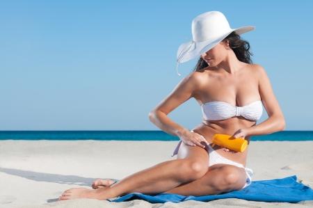 sunbath: Mooie jonge woma toepassing van beschermende lotion voor zonnebaden op het strand