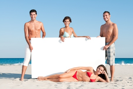 Happy smiling group of friends holding a white board for your text at summer beach photo
