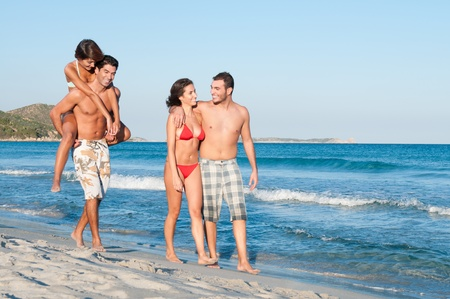 parejas caminando: Dos parejas de amigos caminando por la playa en un d�a de vacaciones de verano Foto de archivo