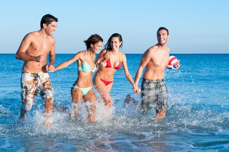Happy couples of friends playing together and running in the water  photo