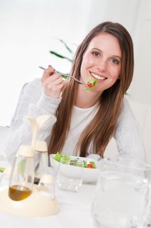 Young beautiful girl eating fresh green salad at home photo