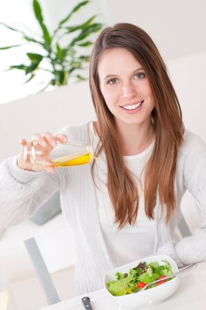 mediterranean home: Happy smiling girl pouring olive oil into her dish of fresh salad Stock Photo