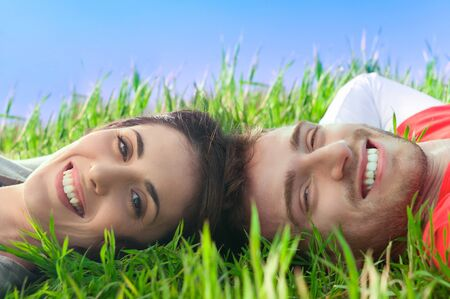 Young happy smiling couple looking at camera lying in the grass outdoor Stock Photo - 9574483