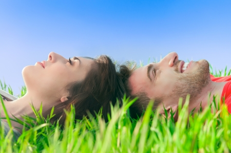 dream vision: Young smiling couple lying down on the grass and dreaming at their future