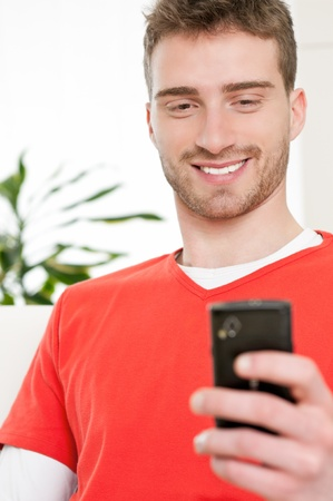 Smiling young man browsing and text messaging on his smart phone at home Stock Photo - 9677707