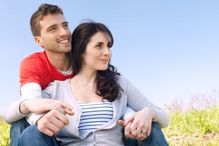 vision futuro: Smilng joven pareja mirando juntos su futuro