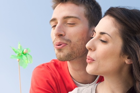 Happy young couple blowing wo move a windmill toy symbol of renewable energy and environmental conservation photo