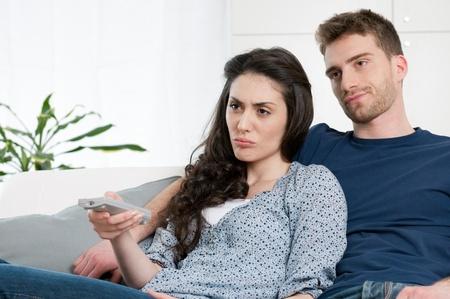 bored man: Annoiato giovane coppia guardando la televisione in casa