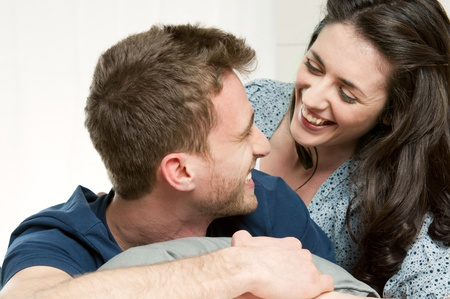 couple laughing: Happy smiling couple laughing together with love at home Stock Photo
