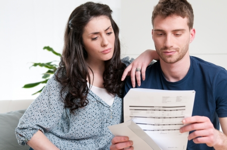 pay bills: Young couple reading a financial bill or letter with worried expressions at home Stock Photo