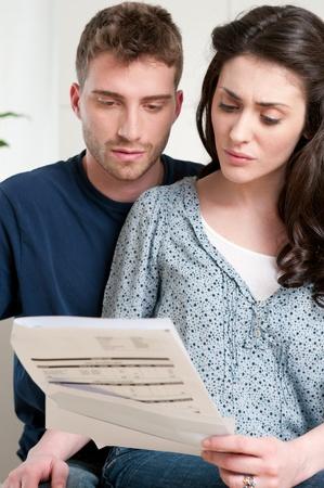 hombre preocupado: Joven pareja lectura un proyecto de ley financiera o carta con expresiones de preocupaci�n en casa