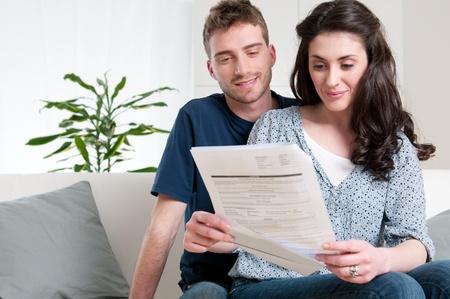 factura: Sonriente pareja lectura un proyecto de ley lleg� por correo