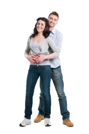 Smiling young couple embracing and standing full length isolated on white background photo