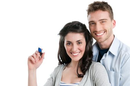 Aimant souriante jeune couple écrire avec marqueur votre texte isolée sur fond blanc