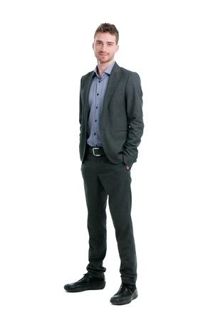 persona de pie: Empresario joven sonriente permanente relajado con las manos en los bolsillos aisladas sobre fondo blanco