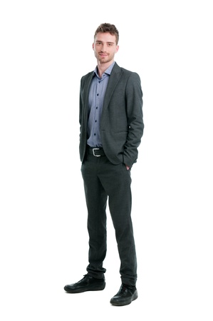 businessman standing: Smiling young businessman standing relaxed with hands in pockets isolated on white background