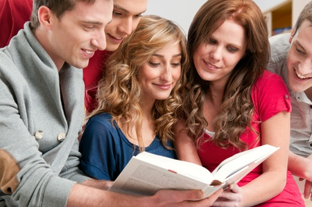 discussing: Happy young college students studying together on a textbook in a library