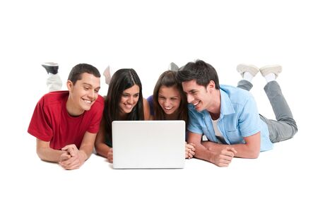 Happy smiling young group of friends watching and working together at laptop isolated on white background photo