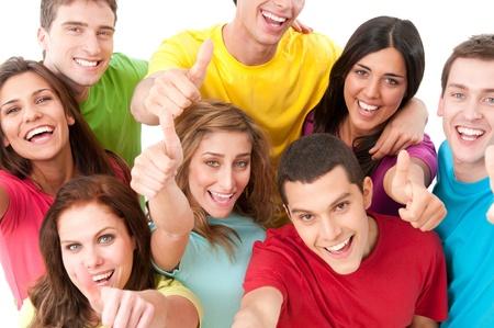 Happy smiling group of joyful friends showing thumb up isolated on white background photo