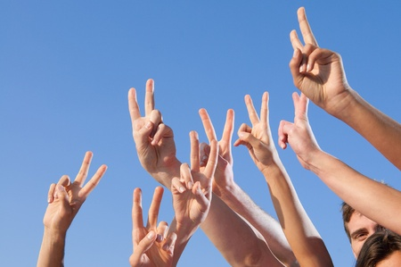 Hand raised with victory sign against blue sky photo