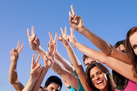 Gelukkig groep jonge vrienden overwinning hand teken tonen over blauwe hemel