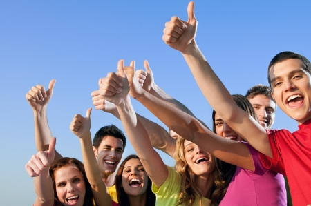 Happy group of joyful friends raising hands with thumb up sign against blue sky photo