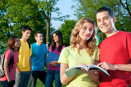 Smiling young group of students studying together outdoor at the college park photo