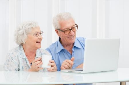 jubilados: Feliz pareja retirado sonriente usando equipo port�til en casa