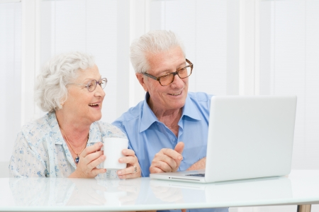 elderly lady: Happy smiling retired couple using computer laptop at home