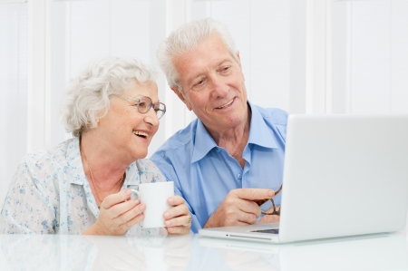 retired: Happy elder couple enjoy together at laptop computer