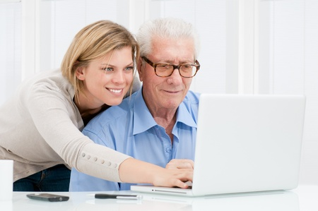 Happy smiling young girl teaching and showing new computer technology to her grandfather Stock Photo