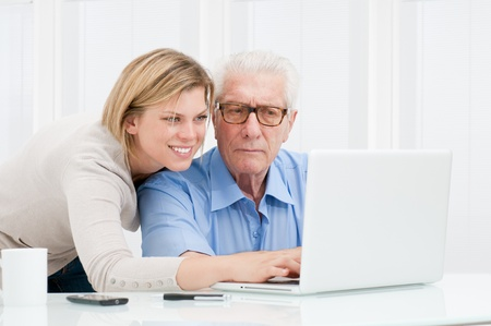 Happy smiling young girl explaining and teaching to her grandparent the use of a modern computer Imagens