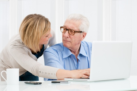education help: Granddaughter helping her grandfather at computer laptop Stock Photo