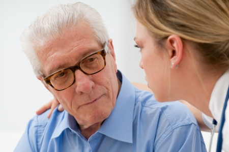 consoling: Sad and lonely senior man with nurse