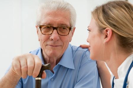 hombre viejo: Enfermera femenina hablando anda teniendo cuidado de anciano senior en el hospital