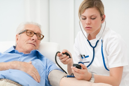 Young nurse checking the blood pressure of her old senior patient at hospital photo