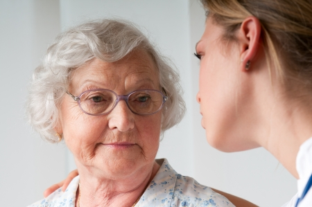 senior pain: Sad and lonely senior woman with nurse  Stock Photo