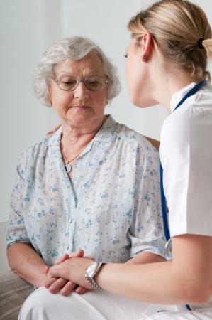 enfermera con paciente: Joven enfermera de consuelo y el cuidado del paciente mayor en el hospital Foto de archivo