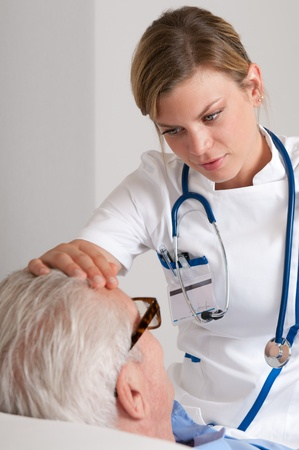 nurses: Smiling young nurse take care of old patient and checking for flu at hospital Stock Photo