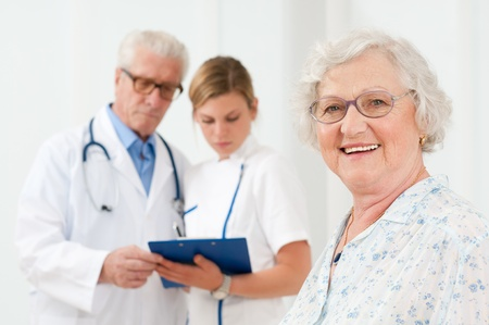 Happy senior woman smiling at camera after her medical exam at hospital photo